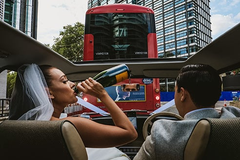 Street Documentary wedding image of bride and groom in wedding car. Groom drives whilst bride drinks champagne from the bottle in passenger seat. Back center is a London routemaster bus with a poster of a man on the back. The eyes of the man in the poster are covered by the rear view mirror reflecting the eyes of the groom.