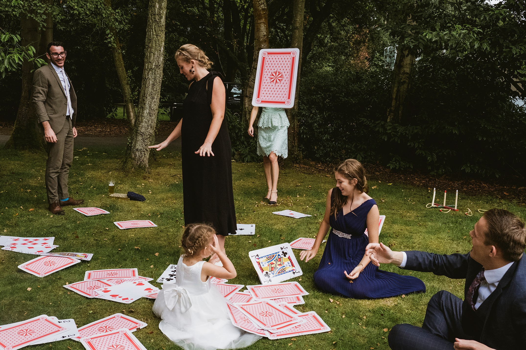 street style documentary wedding image of a group of wedding guests playing with oversized cards during a wedding reception. Central a card flying through the air covers the head and shoulders of a girl in turquoise dress
