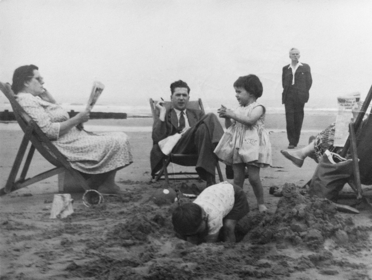 An old black & white photograph from our own family album. Family members on the beach. Woman in deckchair reading paper on right of frame. Man in deckchair who appears to be smoking a cigarette (centre) with young girl to the right of him standing. A young boy in front is digging a hole whilst to the right we can see a man standing in the background smoking a pipe and the edge of the back of another deckchair with a woman's legs poking out and another newspaper in her hands. The sea can be seen in the background.