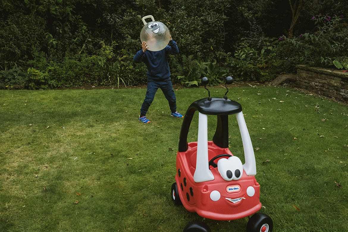 Family Photoshoot in a garden. At the front of the frame is a rideable red toy car with facial features. Behind and slightly to the left a boy stands holding a spacehopper in front of his face. The spacehopper has eyes and a smile, mirroring the face of the car.