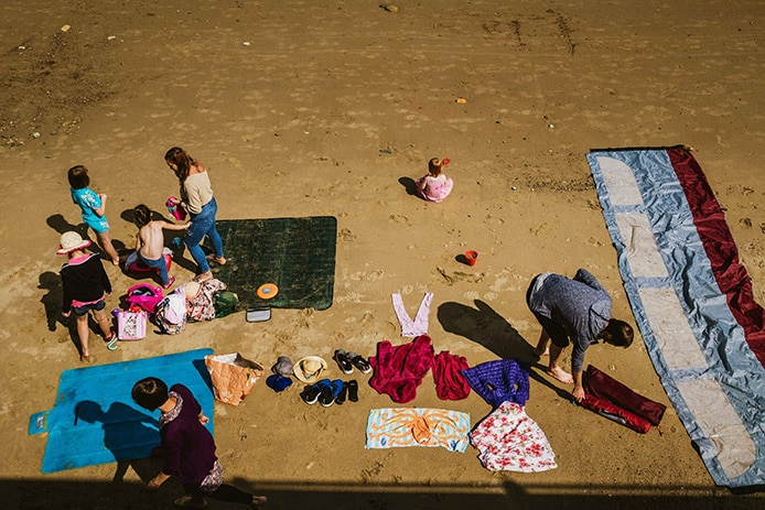 Family Day Out Photography at a beach. Photograph taken from above looking down at the beach where a family have their clothes and wind screen laid out on the sand. A woman is arranging the clothes, to the left a man stands next to a beach towel and in front of him a woman and 3 children are standing. Centre front a little girl sits on her own, cross legged looking out towards the sea