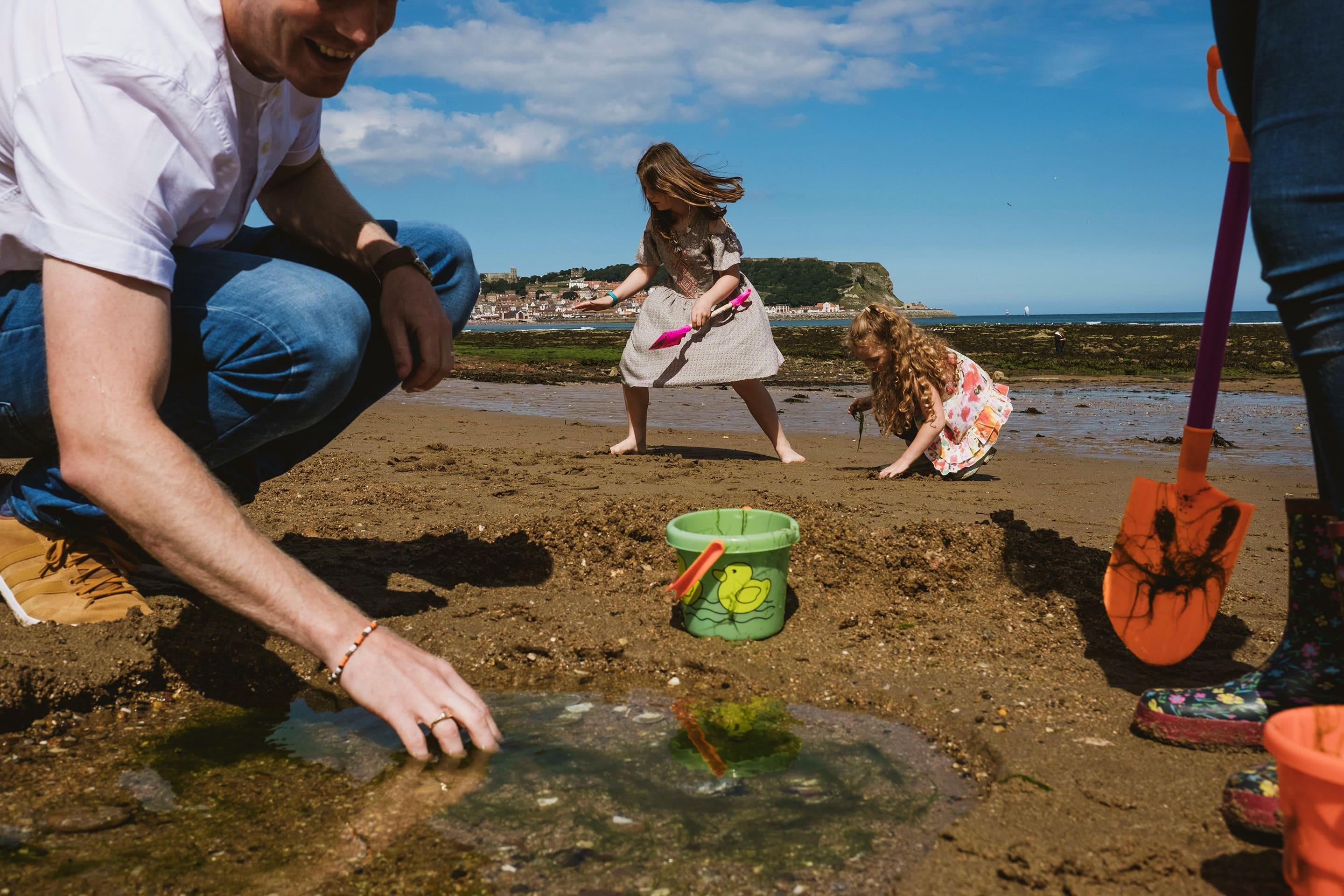 Family Day Out photography on a beach by York Place. A Man is crouched down looking in a rock pool on the left of the image. Next to him is a bucket and opposite someone wearing wellington boots is standing holding a spade with a crab painted on it. In the centre of the frame in the background two girls are playing.