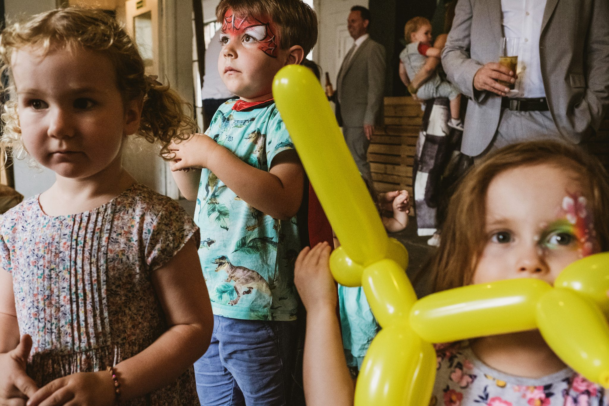 Family gathering photography in London UK. Several children appear in multiple layers of the frame. A girl in facepaint on the left holds a bright yellow balloon animal.