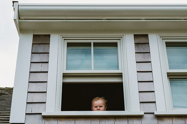 Professional family photograph captured on a family holiday in Nantucket. A small child looks out from an upstairs window in a typical Nantucket home