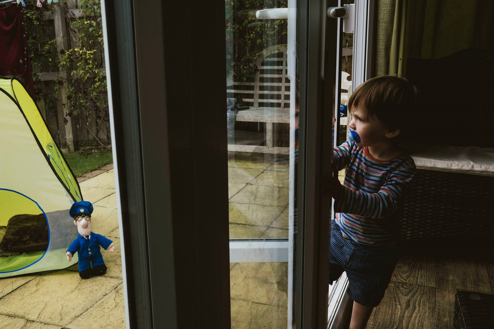 London family at home photography. Little boy with a pacifier stands in the doorway looking out to the garden. Outside is a play tent with a Postman Pat toy leaning against it