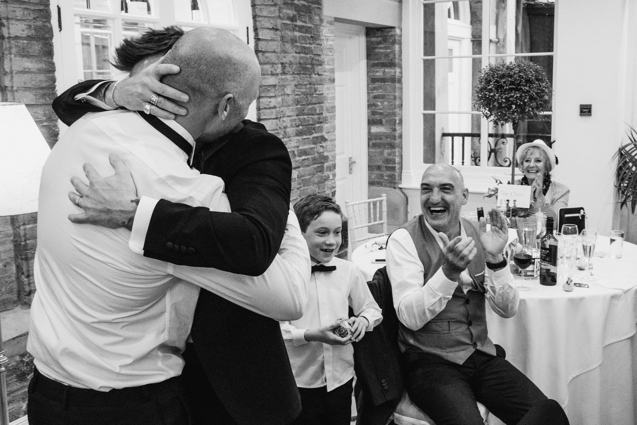 Emotional moment during the wedding speeches. Groom and best man hug each other tightly.
