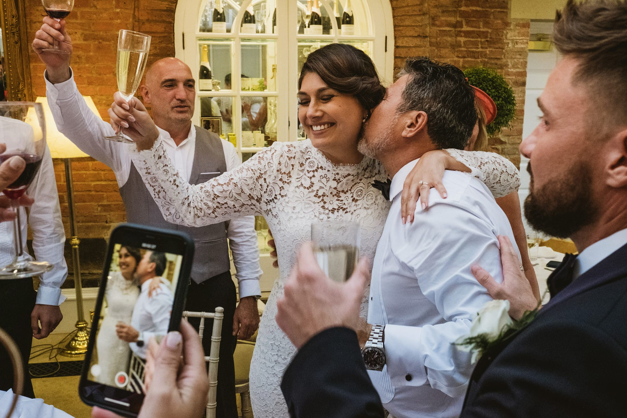 bride celebrating with a glass of champagne in her hand and her dad hugging her