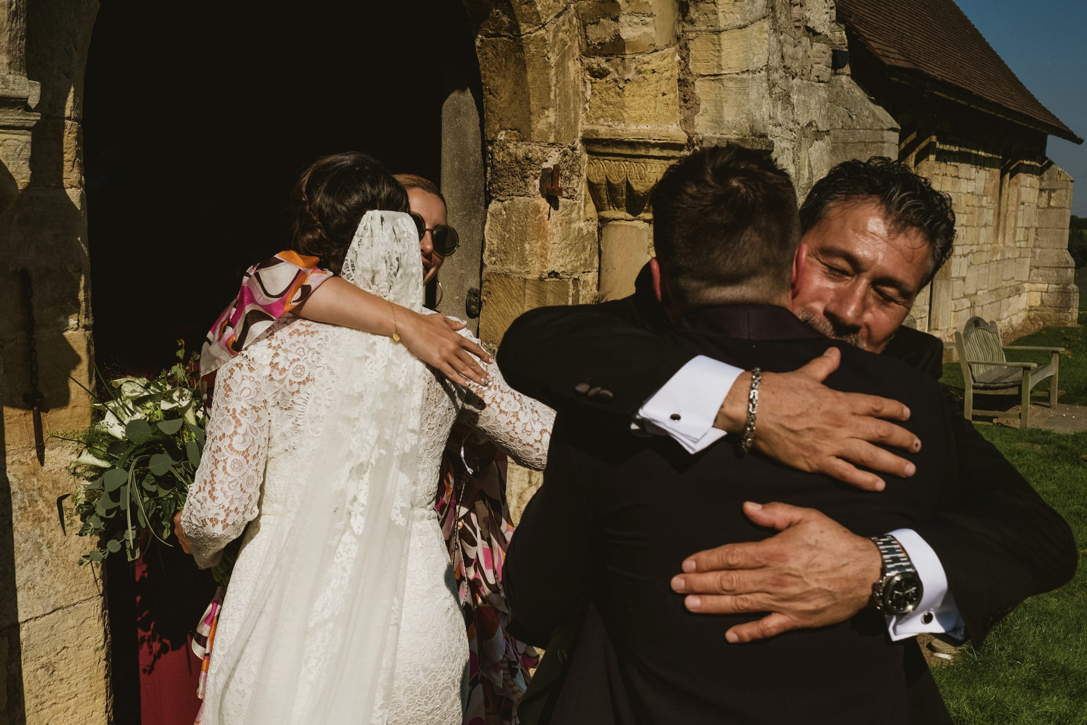groom hugging bride's dad, bride hugging guest