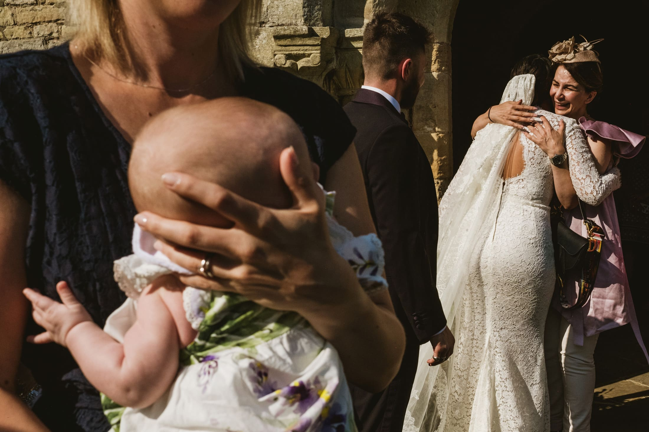 bride hugging guest, baby in foreground
