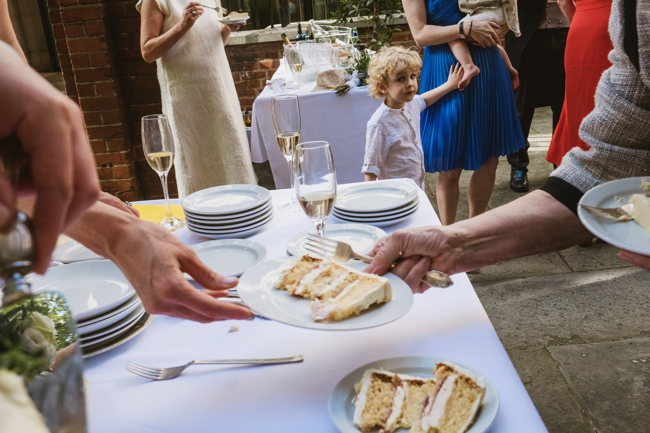 A little boy touches his mum's leg and stares at the camera whilst around him we see the shapes of guests being served cake. No-one else's face is visible. Unposed documentary wedding moment photographed by York Place Studios