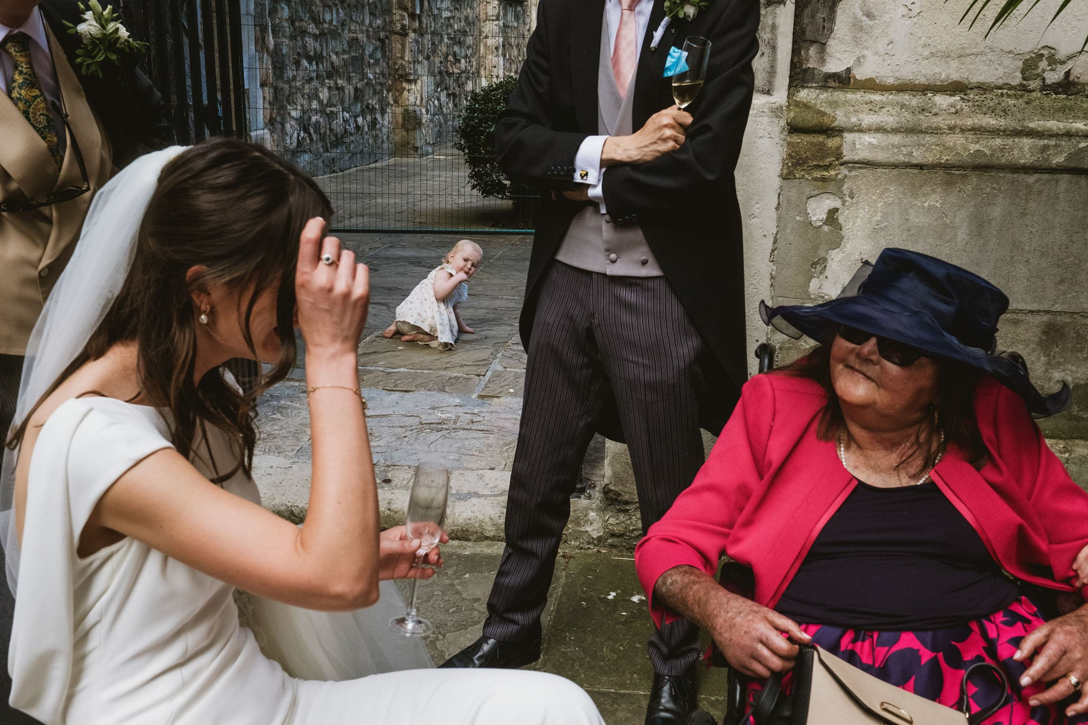 London street wedding photography scene. A little girl in the background, creeping towards the exit, is framed between the bride, groom and guests. Only the little girl's face is fully visible as she looks back towards the camera