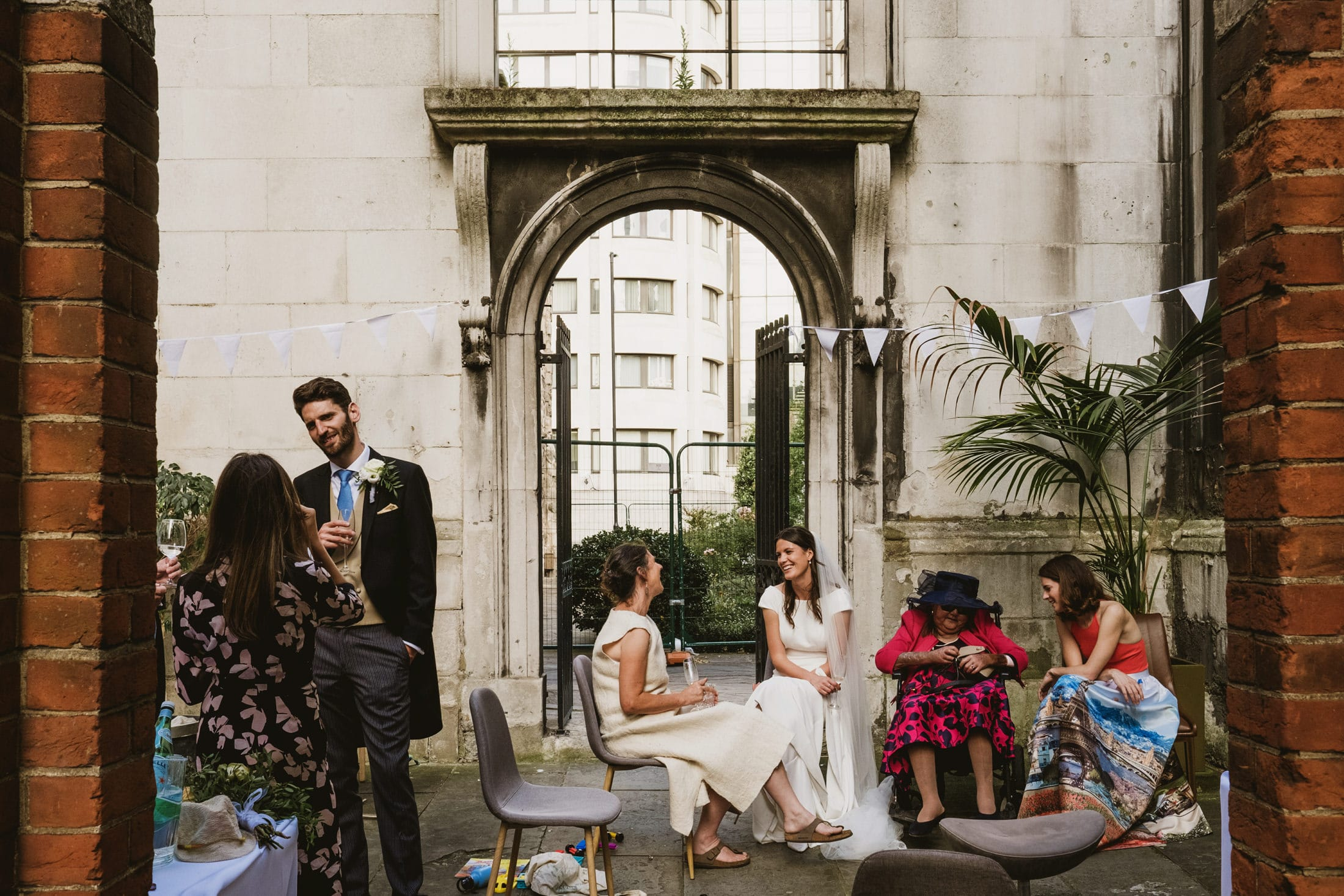 Multiple guests interact with the bride and groom at an intimate London Micro wedding reception. Photo captured at a slight distance, framed by two brick columns either side.