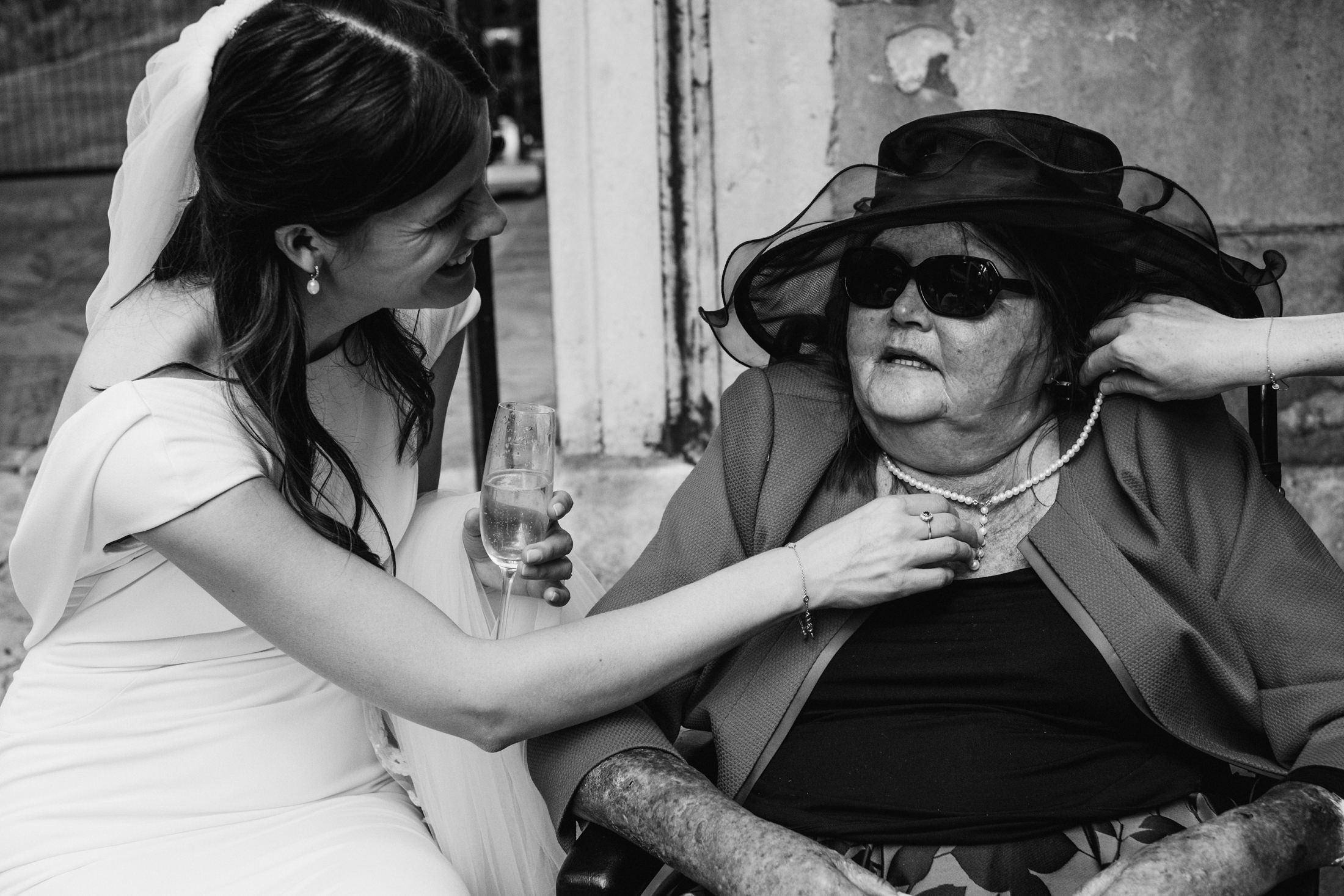 Black & white wedding photography. A bride lovingly inspects the necklace worn by an older female guest.