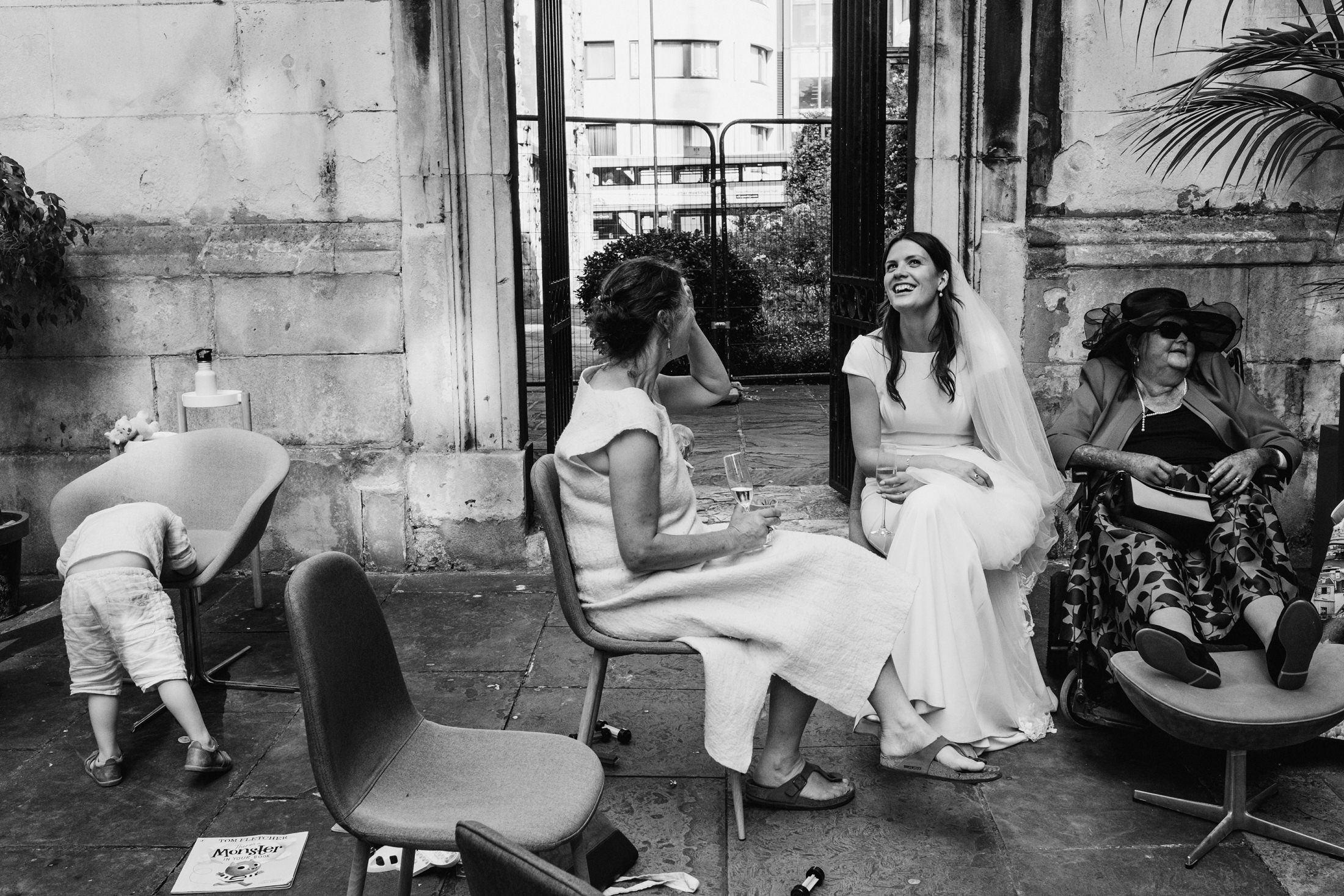 "In a courtyard at an outdoor wedding ceremony in London a smiling woman in sunglasses (right) rests her feet on a footrest. Beside her the bride smiles in conversation with a female guest. On the far left of the image a little boy with his back turned to camera has placed his face on a chair, making an unusual shape. On the floor in front of him lies a book with the title ""Monster"" written in bold upon it"