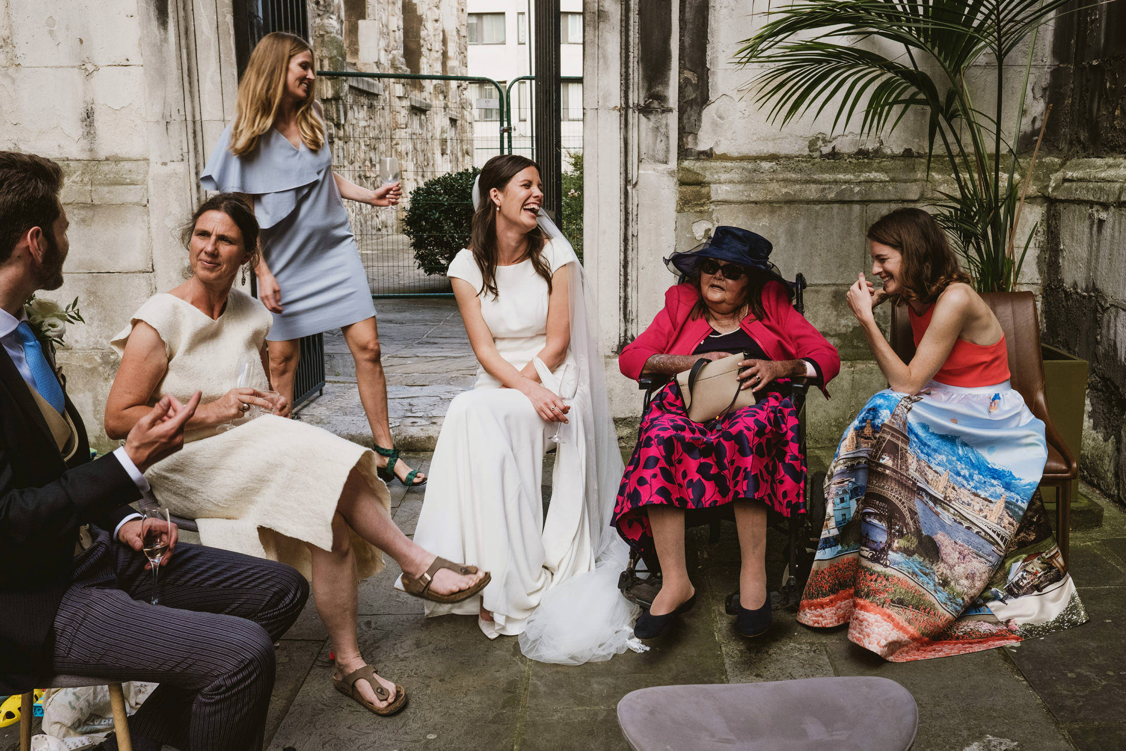 A bride is seated in the centre of the frame at an outdoor wedding in London. She laughs along with the two seated guests to her left. To her right a woman stands in the background as she comes to join the conversation, whilst beside her, closer to camera, two more seated members of the wedding party interact.