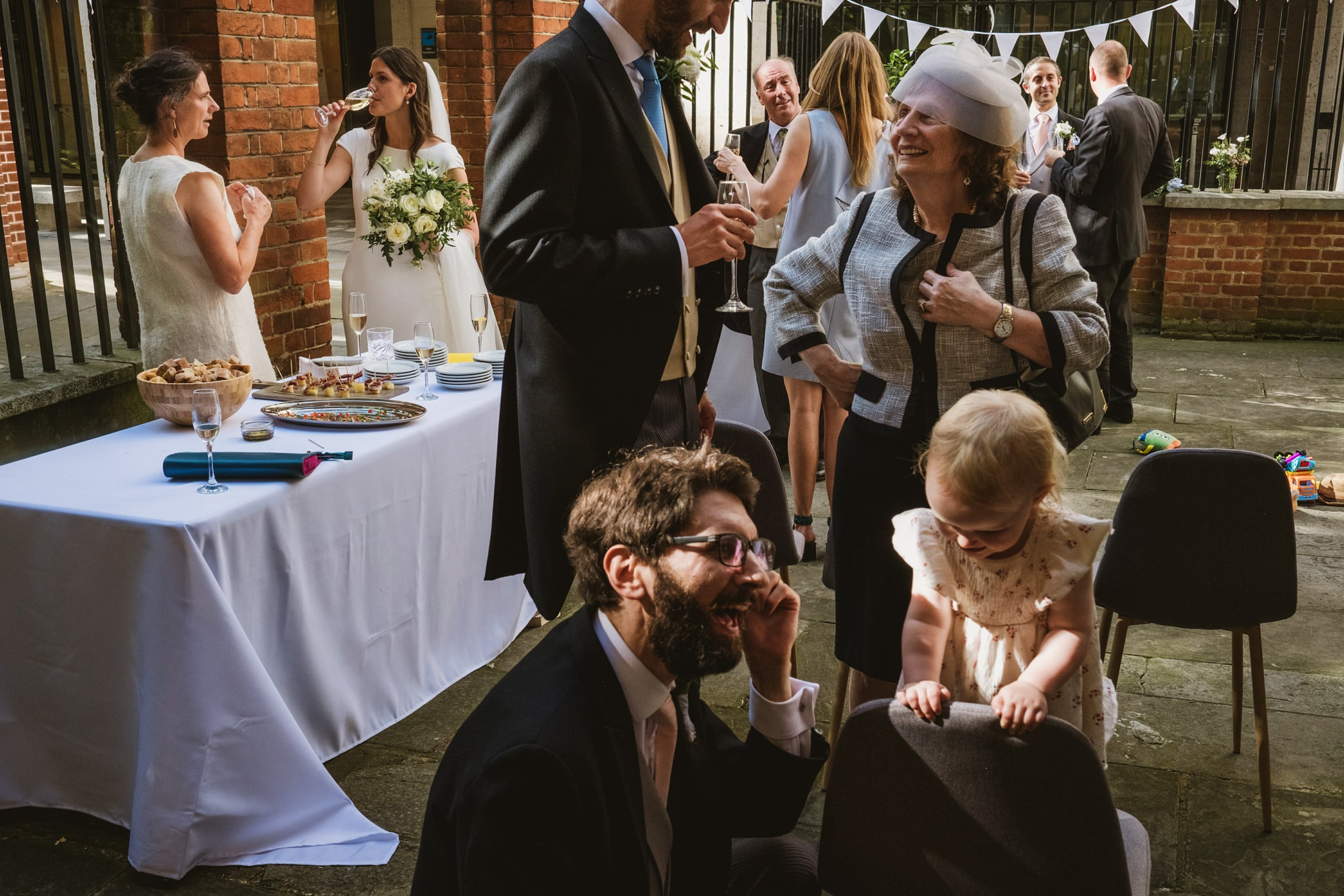 Guests interact at an intimate London wedding. To the left the bride sips champagne whilst in conversation with a female guest as they stand behind a table. Beside them but in the foreground the groom, his face not visible, separates the frame as he talks to a smiling woman beside him. Framed either side of them in the background other guests share private conversations whilst at the very front of the image a man crouches down to the height of the child next to him and both appear to be laughing