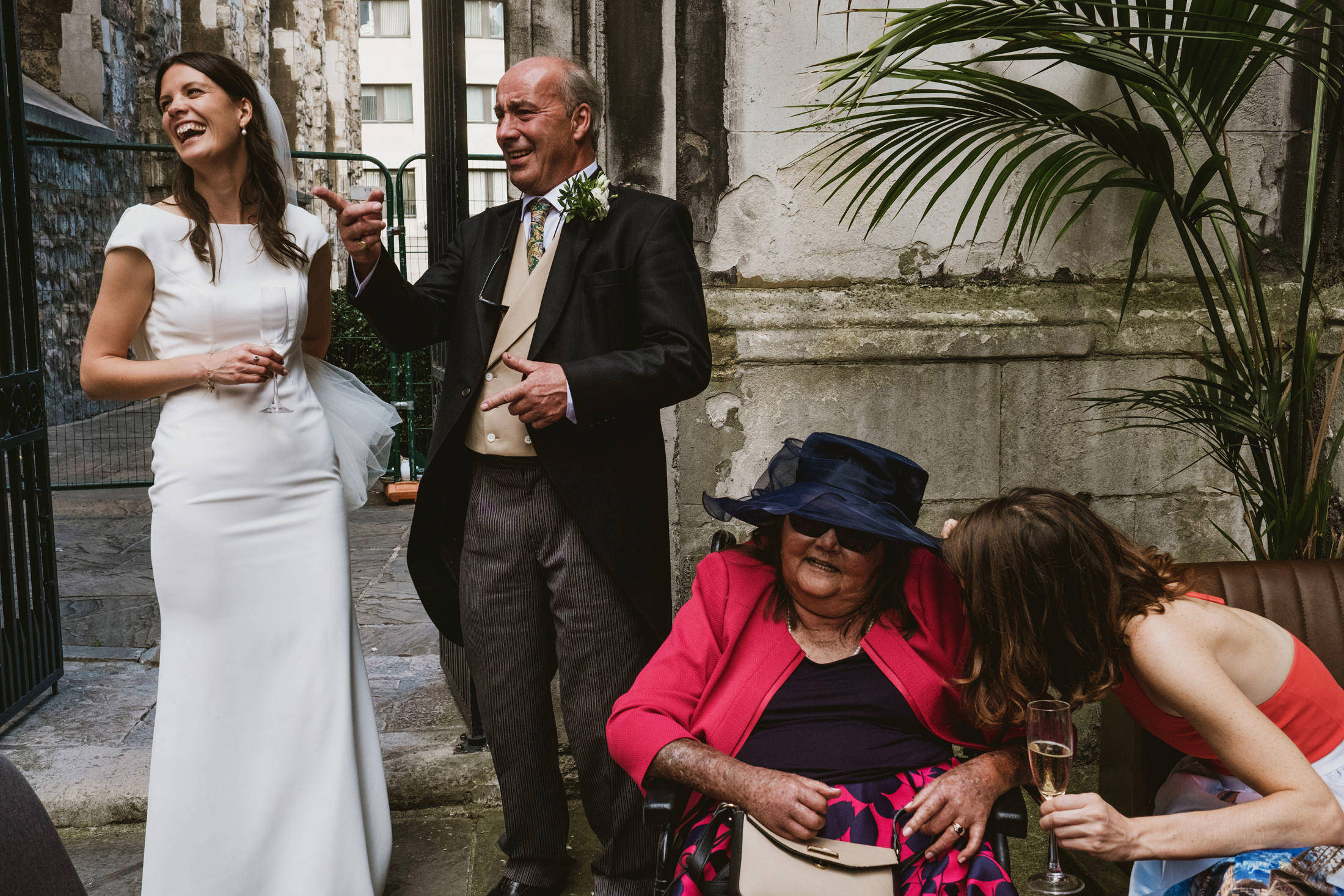 Bride and her father stand and laugh at an unseen joke whilst to their left a seated bridesmaid and family member converse. Documentary style wedding photograph