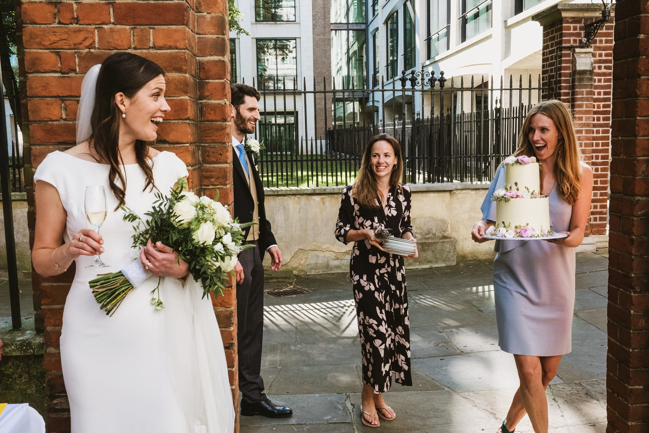 A tiered wedding cake is unexpectedly revealed by a guest during an intimate outdoor micro wedding in London