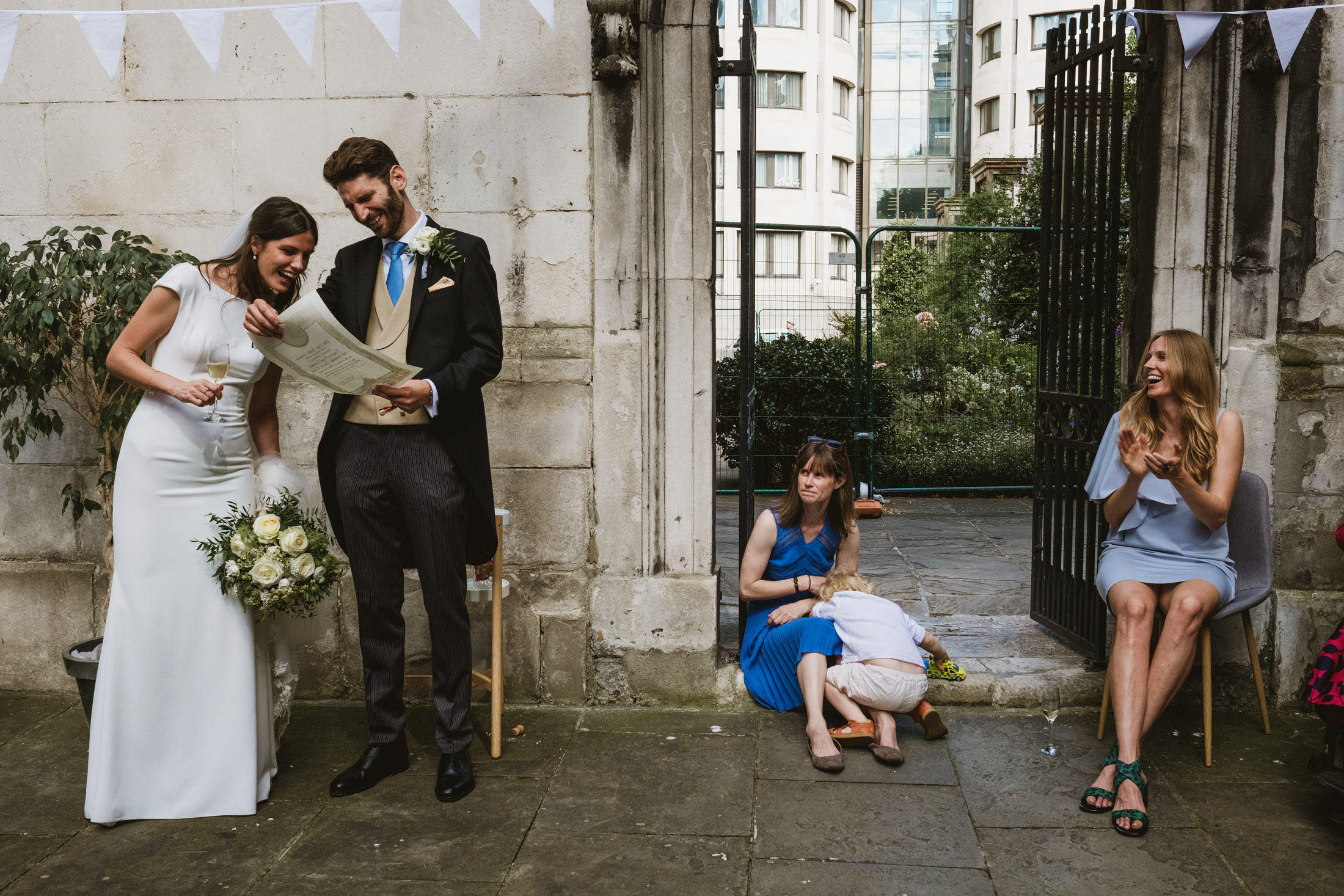 Bride and groom inspect their marriage certificate during their intimate wedding reception in London, photographed by York Place Studios