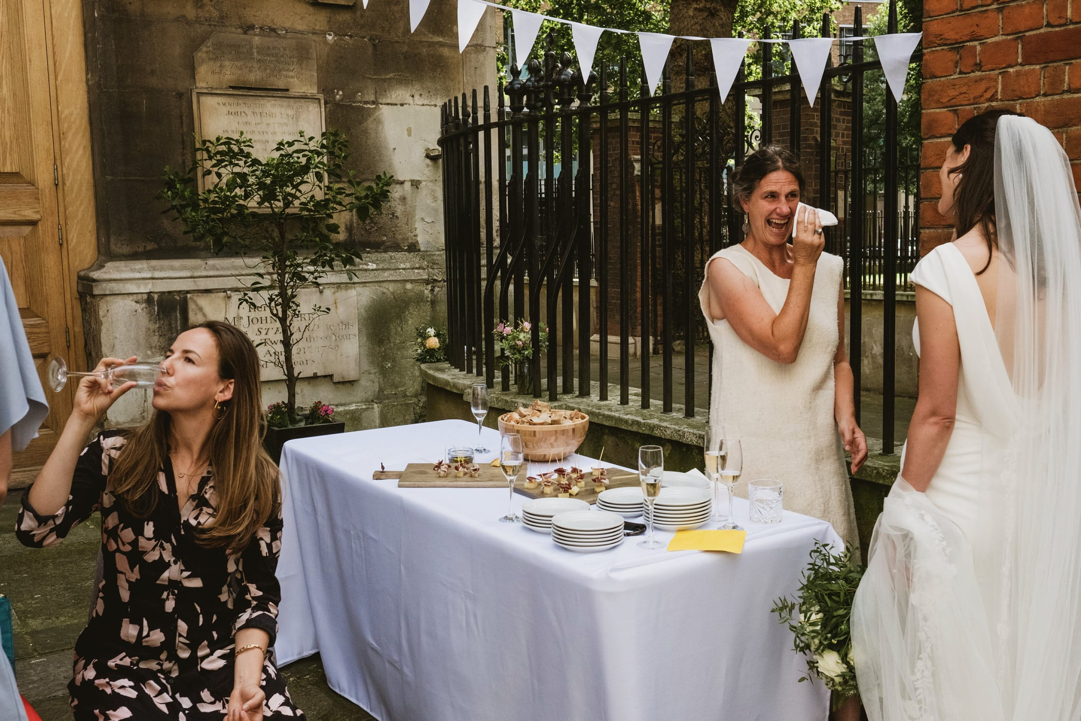 Female wedding guest holds a tissue to her eye as she laughs and cries with the bride. They stand beside a white clothed table of food, another seated female guest taking a drink of champagne beside it.