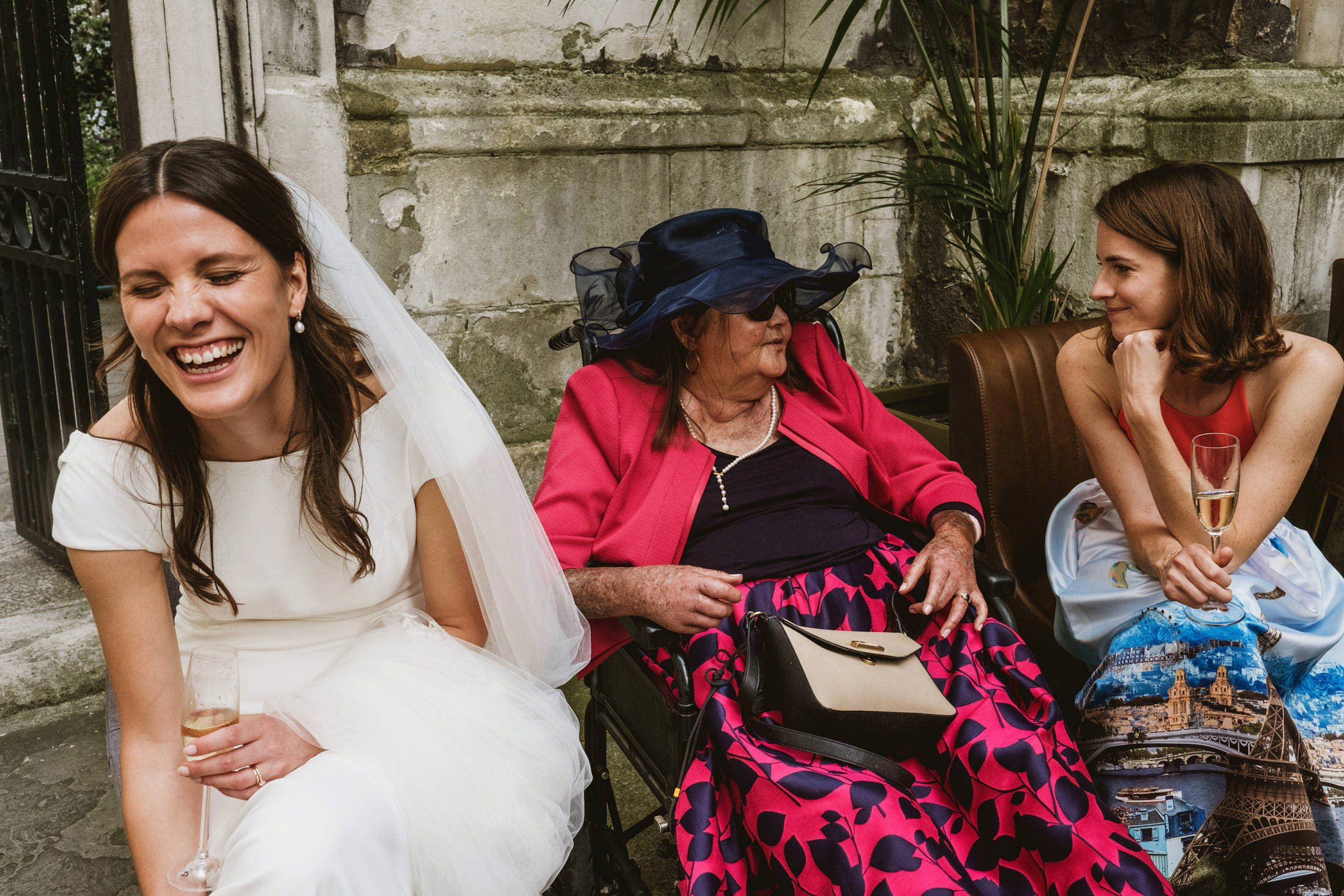 (Left) a bride sits laughing with someone outside of the frame. To her left two seated guests enjoy a conversation