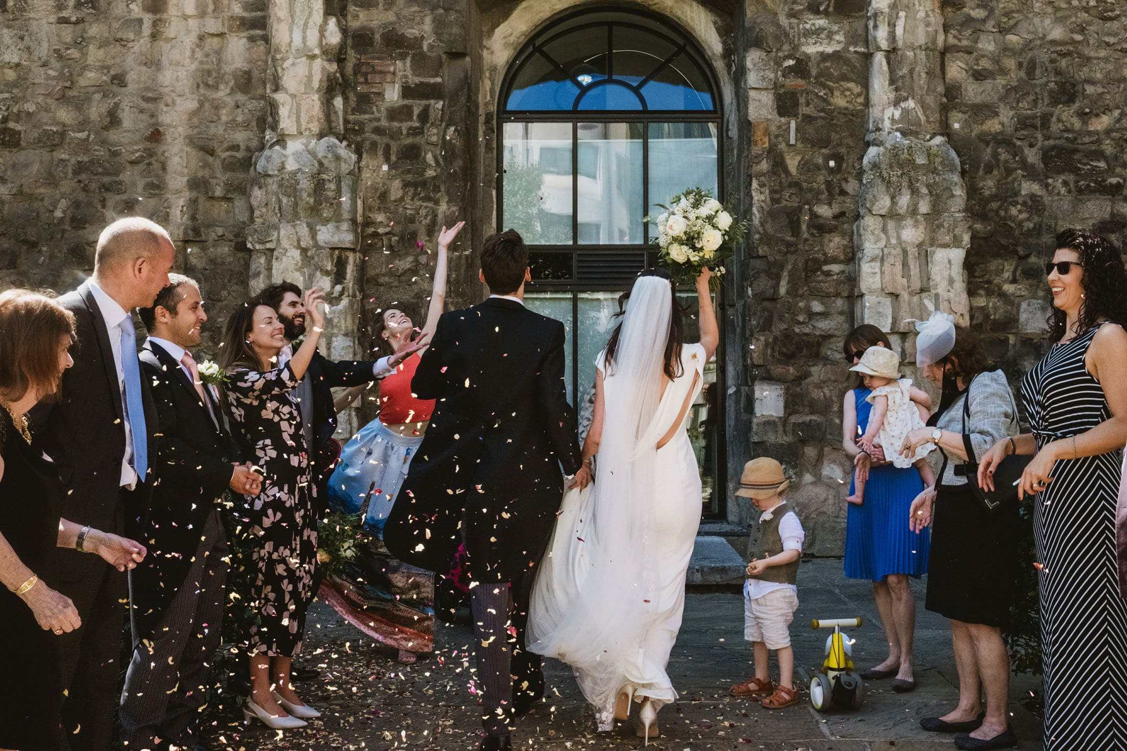 Bride and groom walk back through a confetti line following their micro wedding ceremony