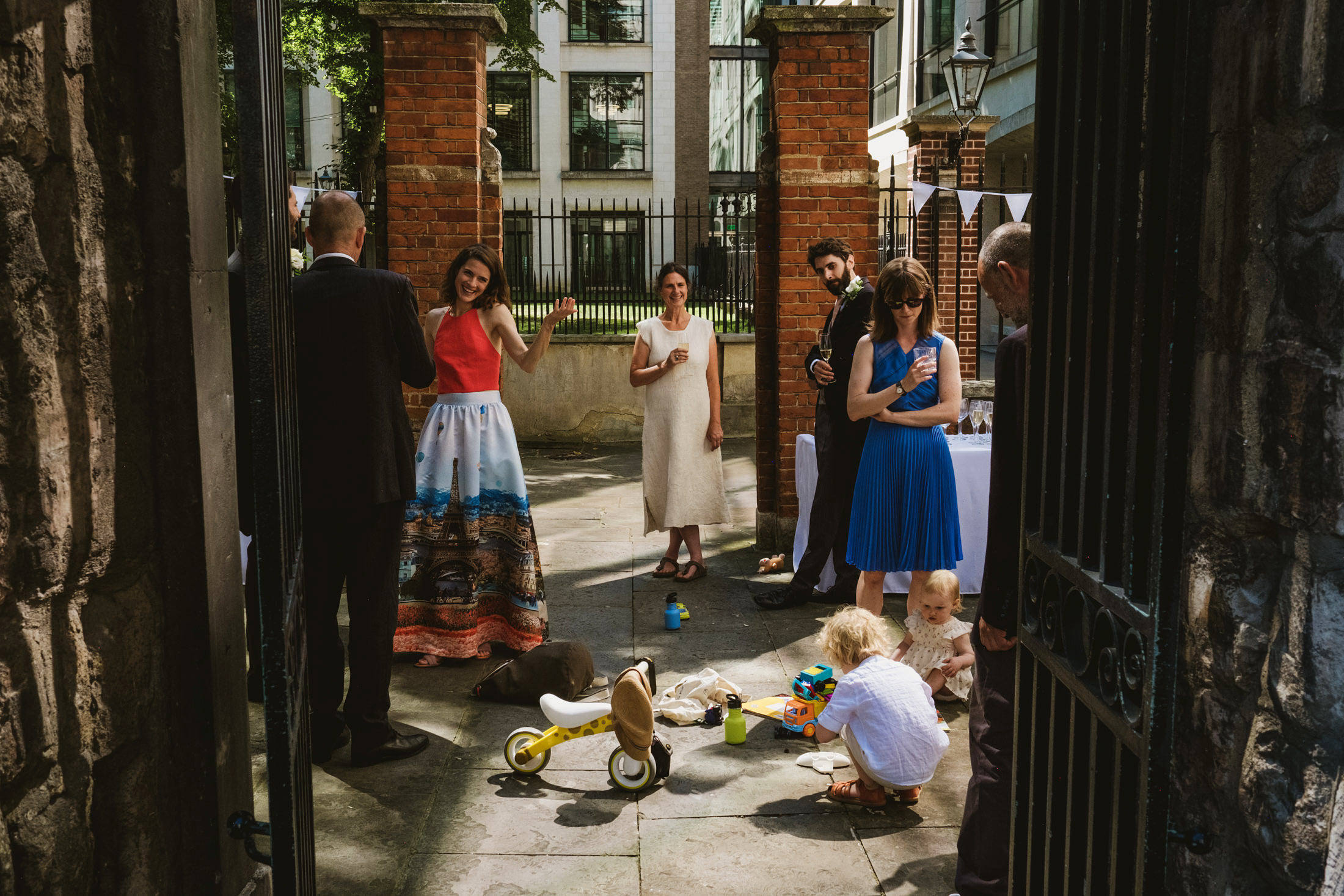 Layered street style wedding photograph of guests gathered for a micro wedding reception framed by the gates of Greyfriar's Passage, London