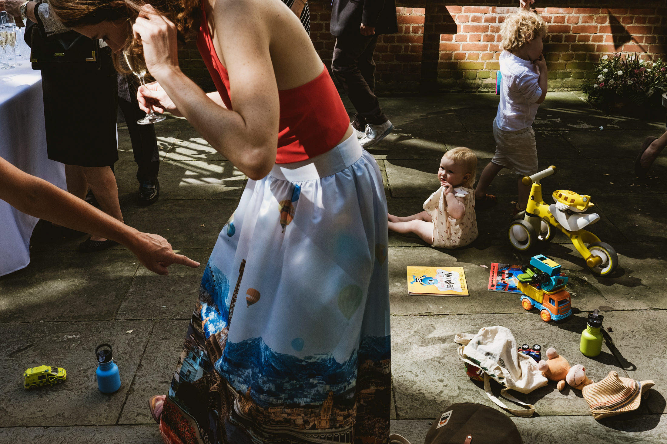 A hand points to a bridesmaid's unusual Paris skyline dress, the bridesmaid's face cropped out of the frame. To the right a little girl sits on the ground next to a yellow tricycle. Other guest's legs, feet and various toys are scattered between, filling the frame.