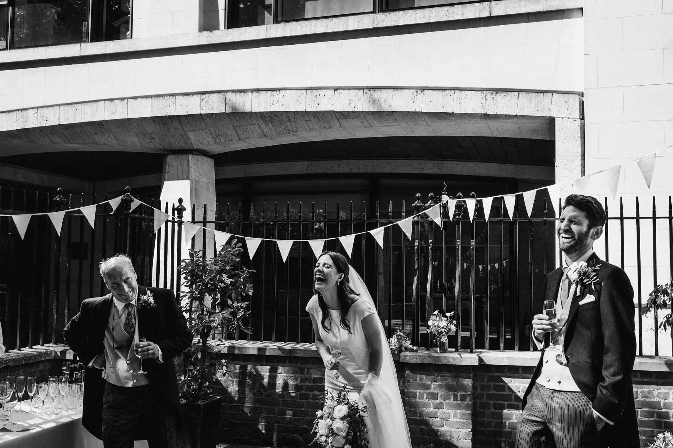 Bride, groom and father of the bride laugh hysterically during wedding speeches in Greyfriar's passage. Monochrome wedding photograph