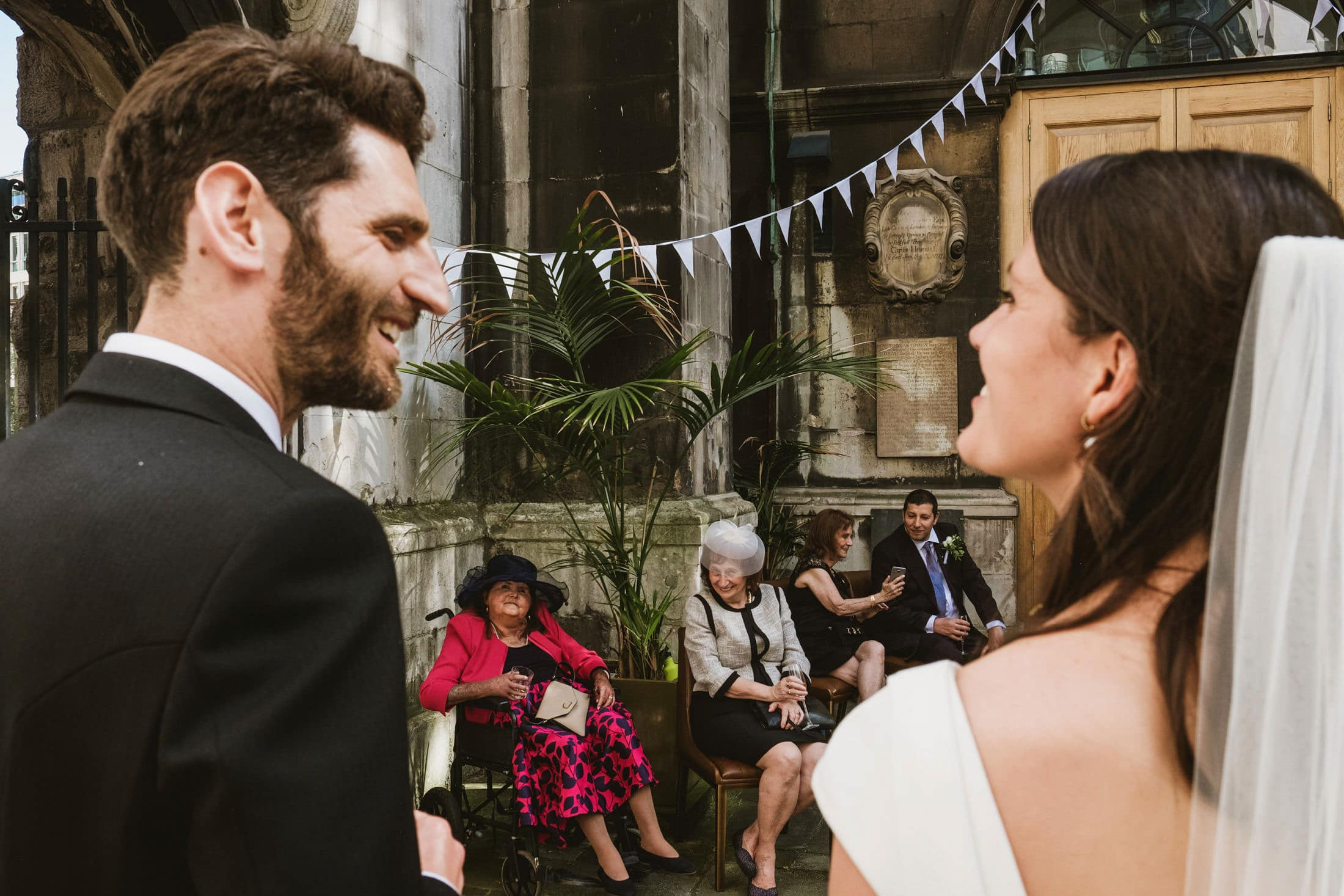 in the foreground a bride and groom, their backs to camera, look at each other across the frame. Between them in the background a section of bunting hangs down, beneath which are four seated guests
