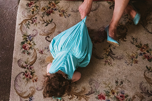 Example of humour in documentary wedding photography. Photographed from above - Girl lays on the floor and is prevented from crawling off by her mother's hand holding the back of her turquoise dress. The mother's shoes are colour matched to the dress and only her feet and hand can be seen in the top right corner of the image.