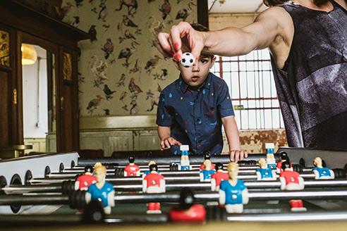 Humour in reportage wedding photography example 3 - Boy plays table football, standing facing towards camera in back of image with table in front of him. To the right of the frame a female guest holds out the ball ready to drop it onto the table. The ball perfectly covers the eye of the young boy.