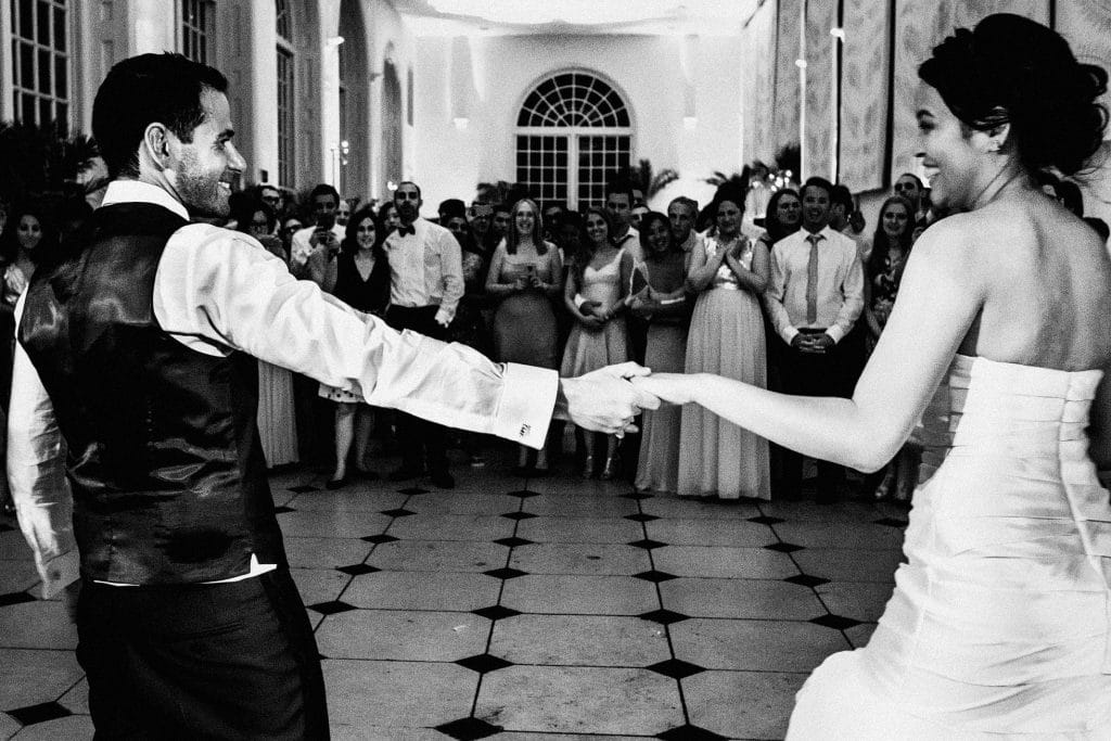 Couple hold hands during first dance in front of their guests in the Orangery at Kew Gardens London. Black and white wedding photography
