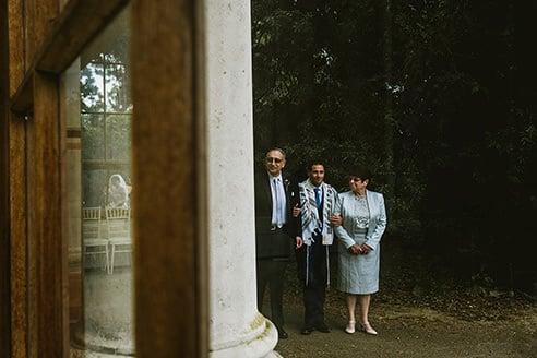 Kew Gardens wedding ceremony. Bride reflection and groom waiting to go into ceremony.