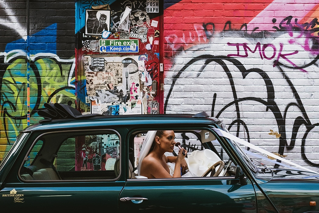documentary style wedding photograph - bride touches up makeup in mini wedding car in front of a graffiti wall background on London street