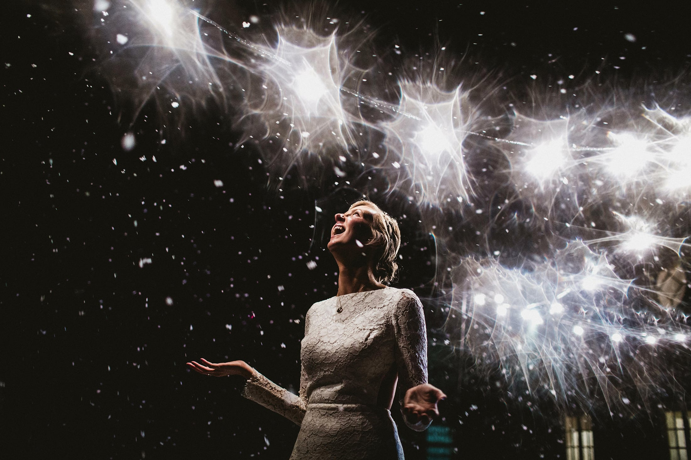 bride looking up at snowflakes falling all around her