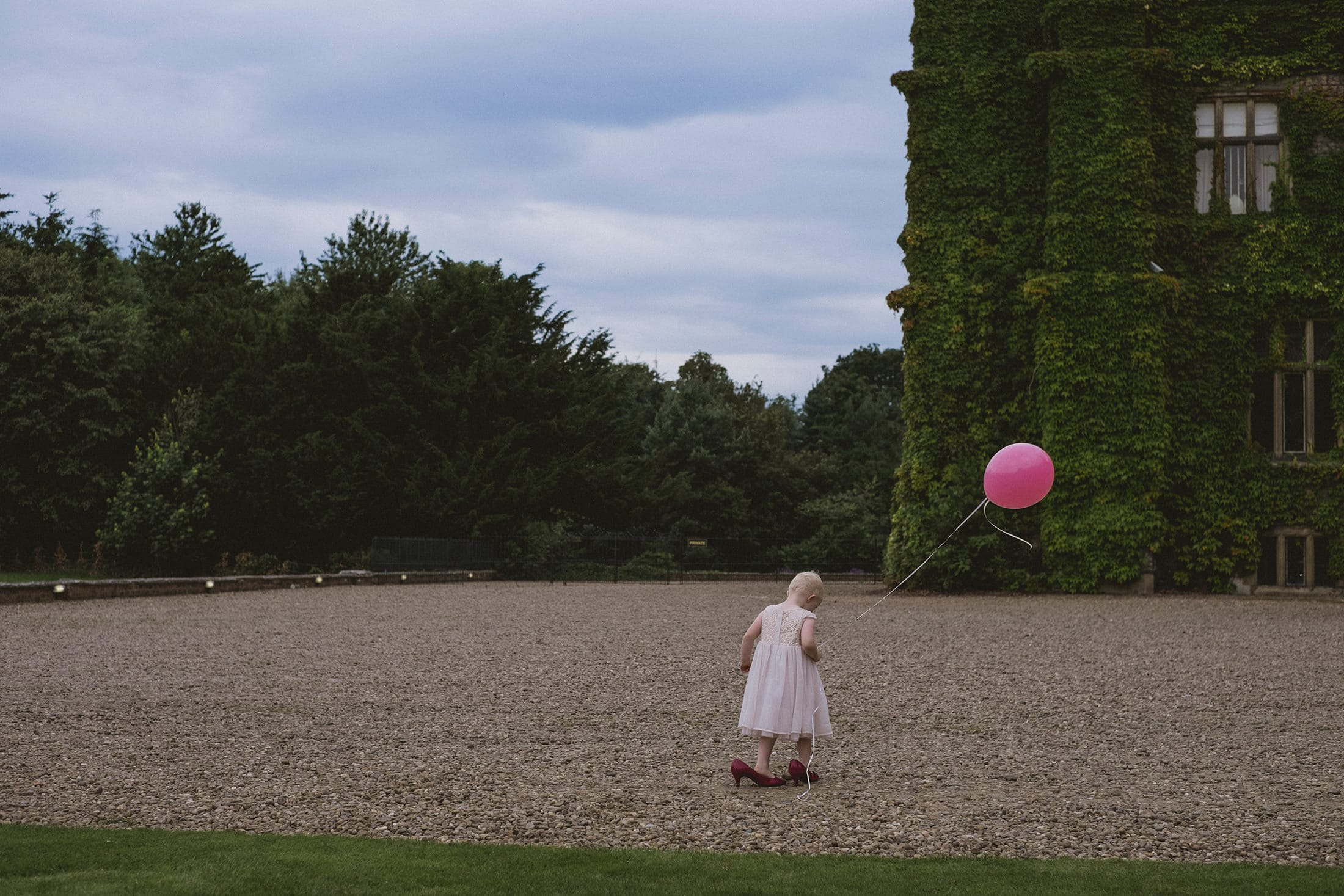 little girl in pink dress walking in high heels holding a balloon