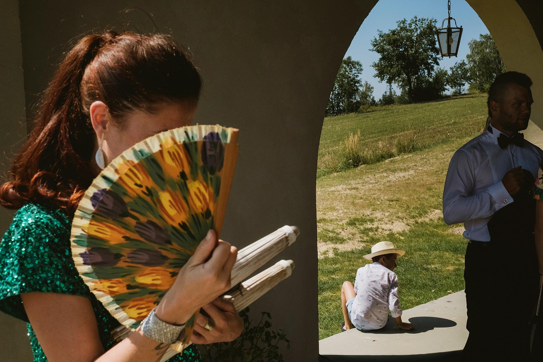 woman hiding behind a fan