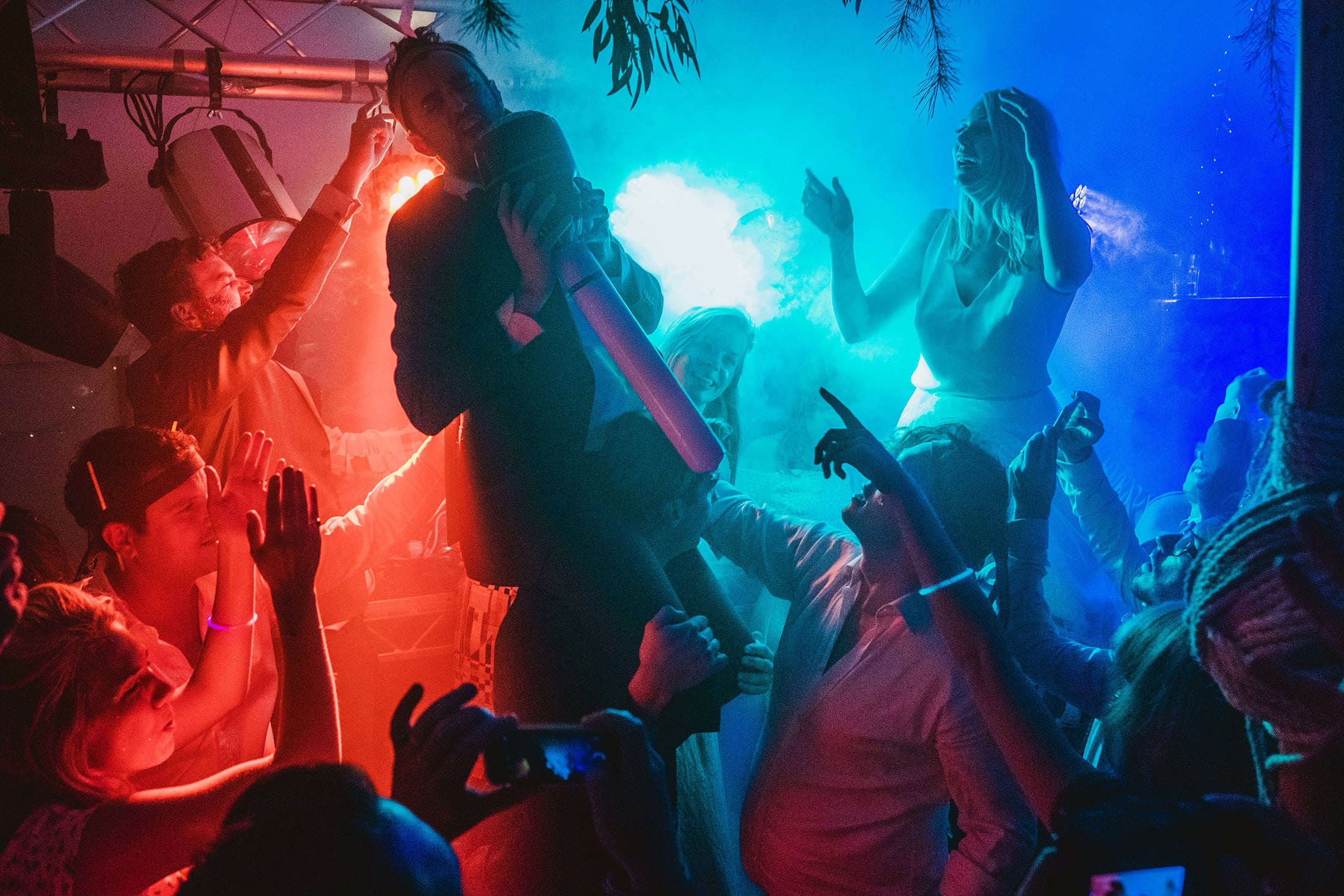 dance floor lit up with blue and red lights, bride and groom lifted into the air by friends