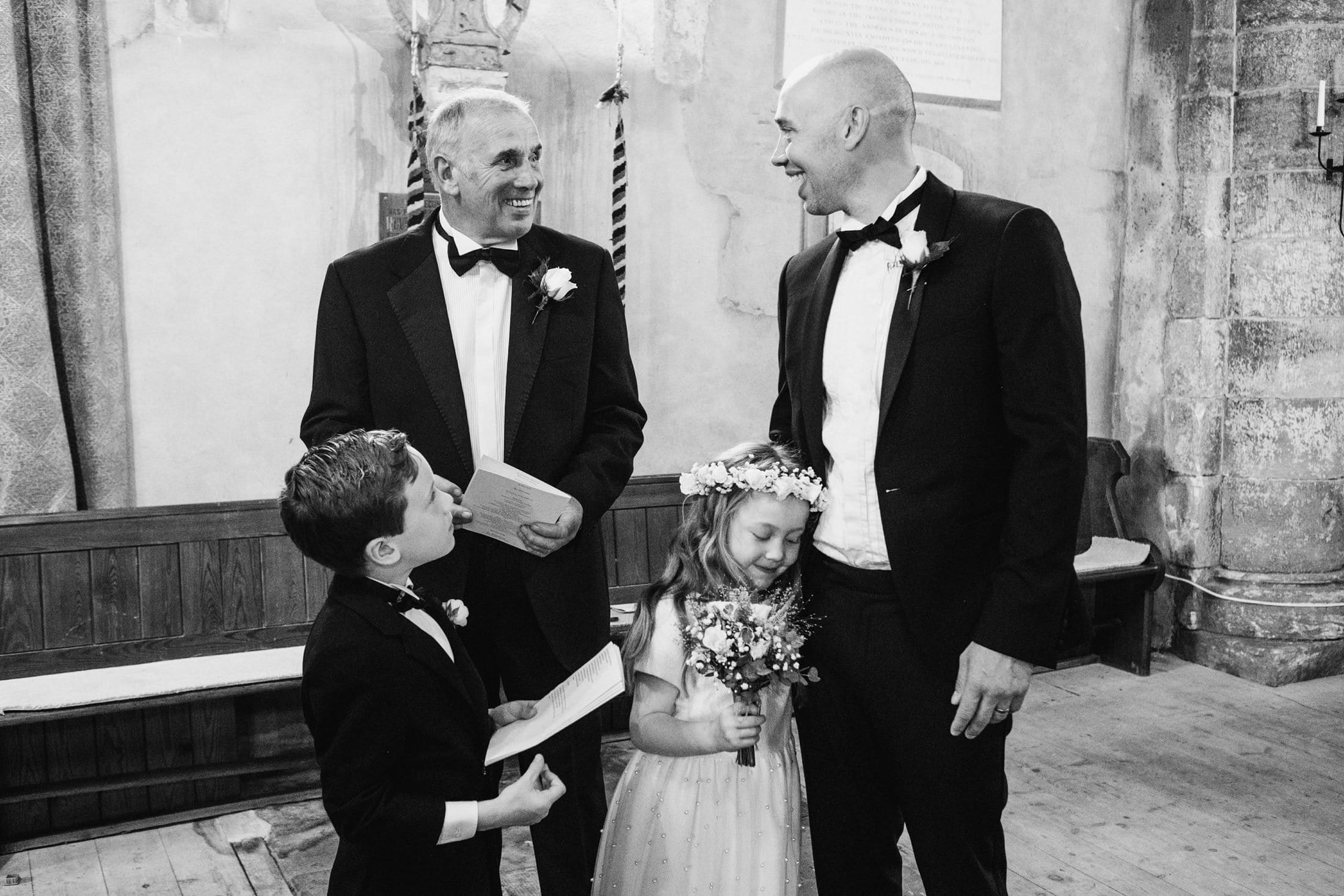 wedding guests, flower girl and page boy. Flower girl hugging dad's knee