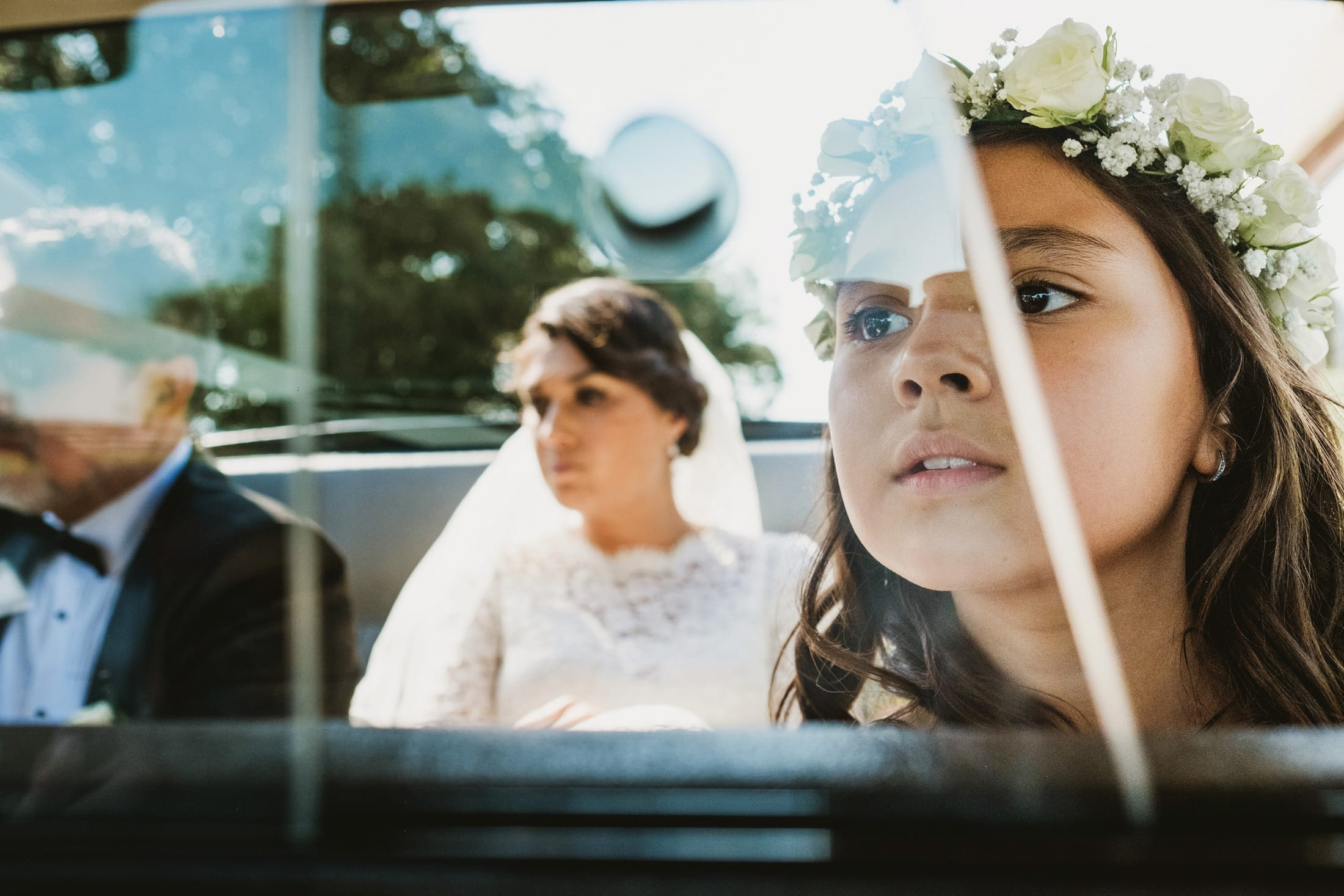 bride, dad and bridesmaid in car. Bridesmaid in the foreground.