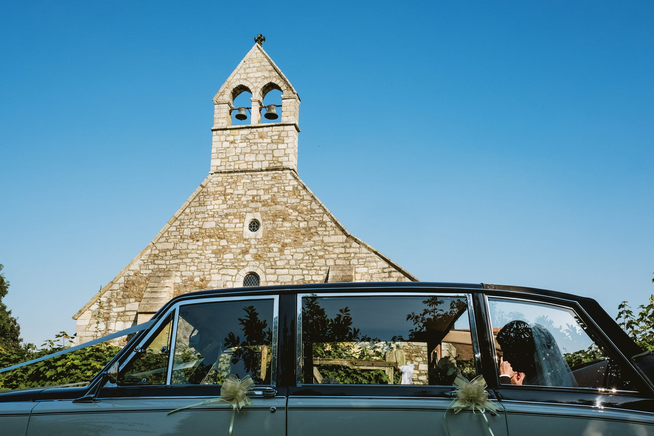 bride and groom in car with church in the background