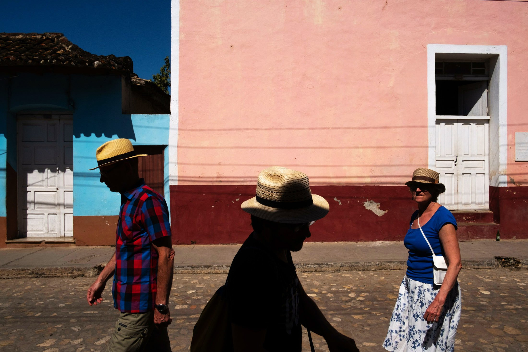 three people wearing hats in shafts of light in Trinidad, Cuba