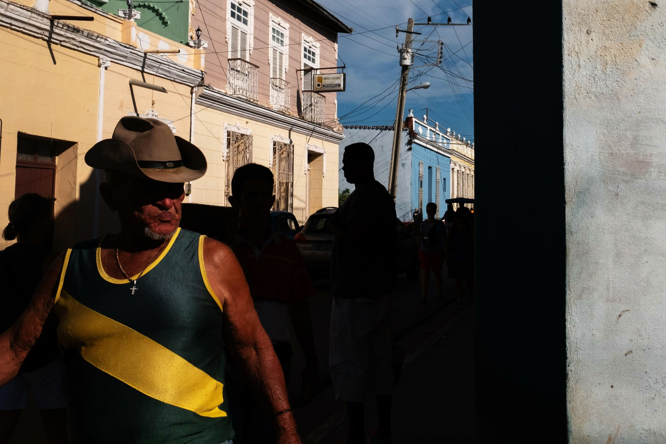 man in cowboy hat wearing green and yellow striped vest
