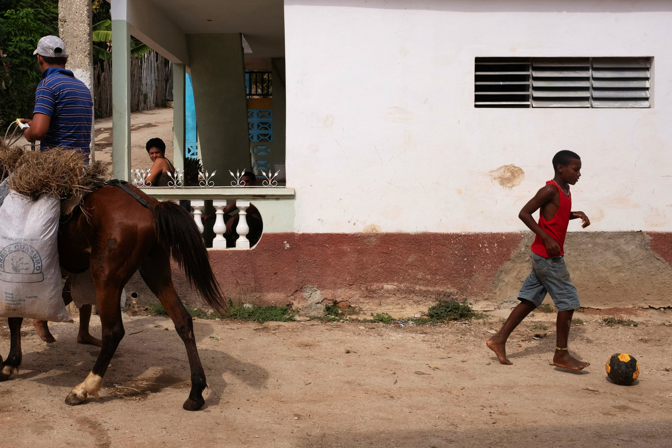 boy playing football in Trinidad with a backside of a horse showing