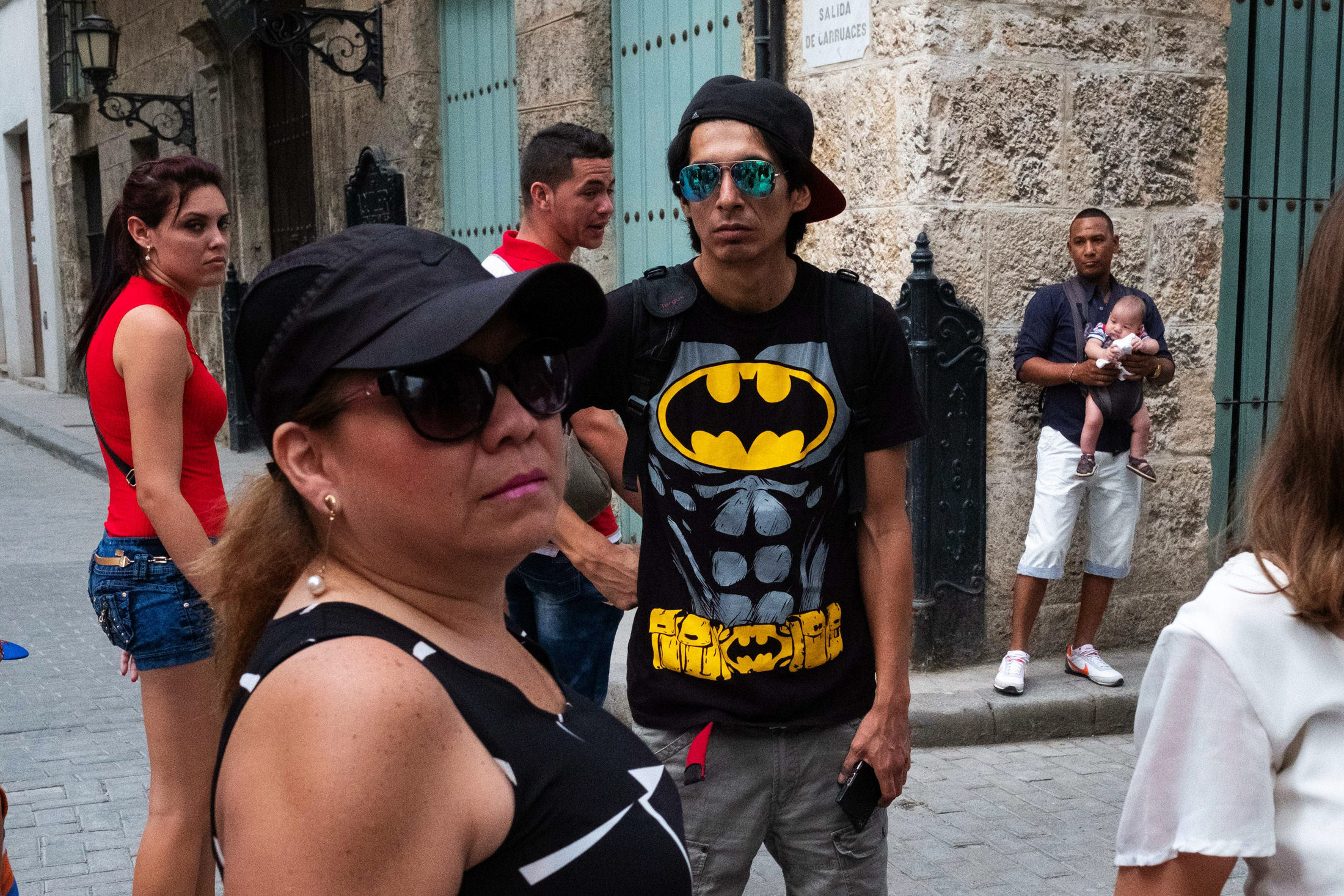 man wearing a bat man t shirt staring at the camera surrounded by a crowd of people