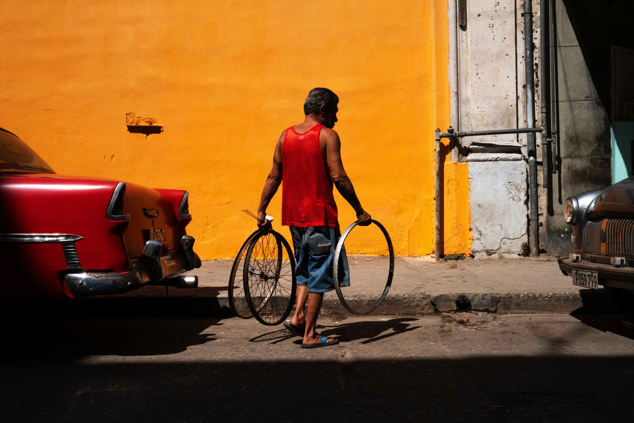 man holding two bicycle wheels against a yellow wall