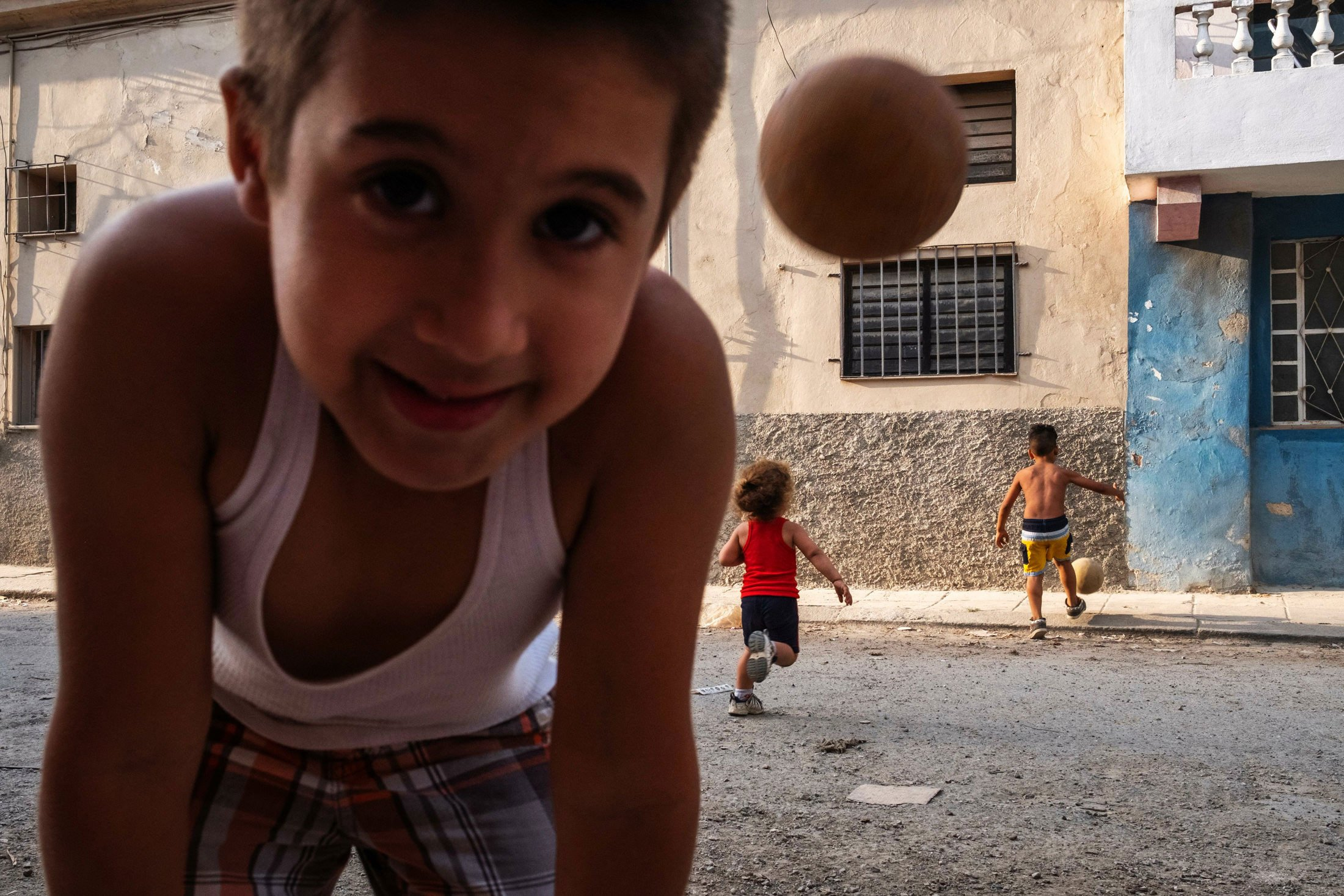 boy leaning into the camera with two boys playing football in the background