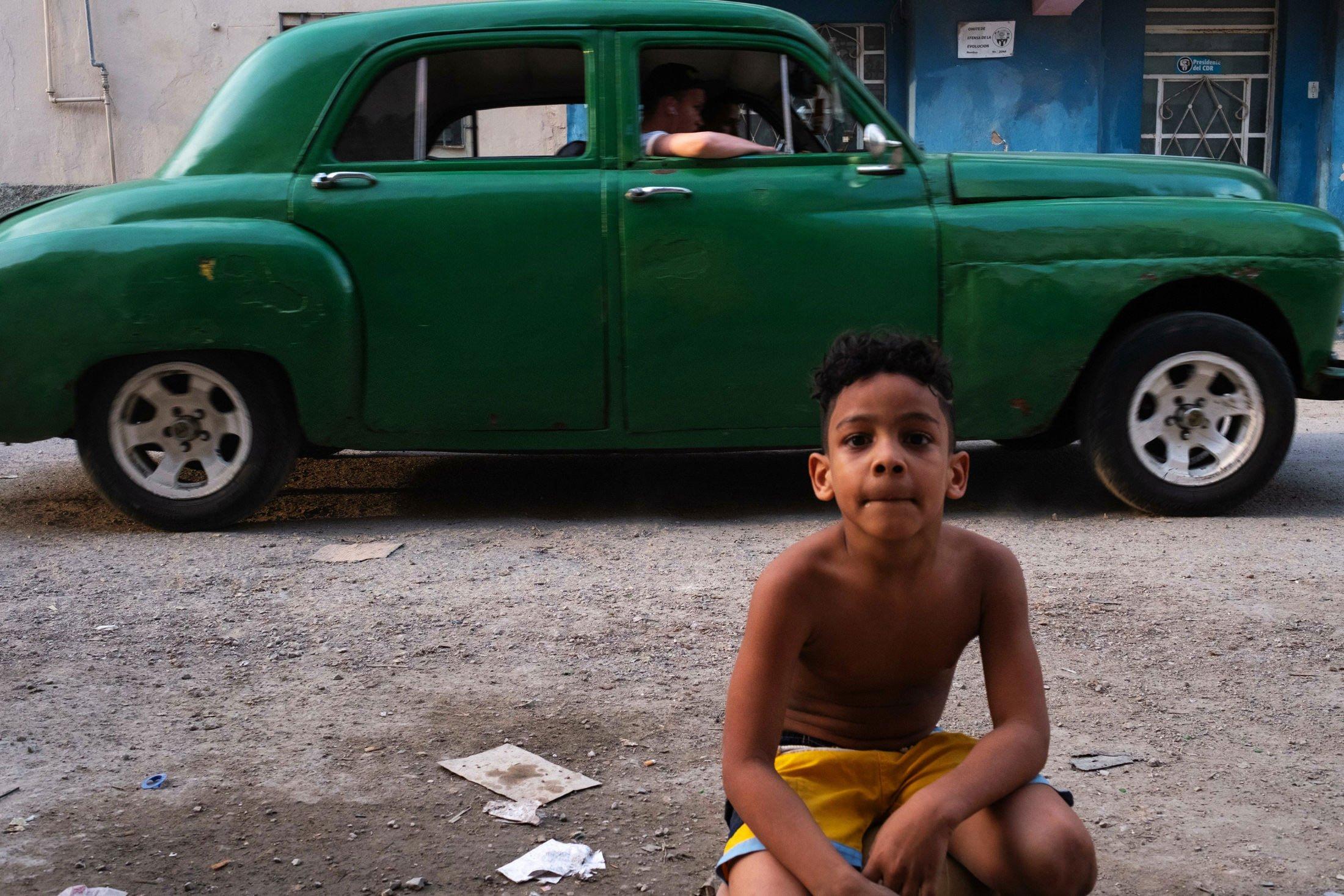 portrait of a boy sat next to a green cuban car