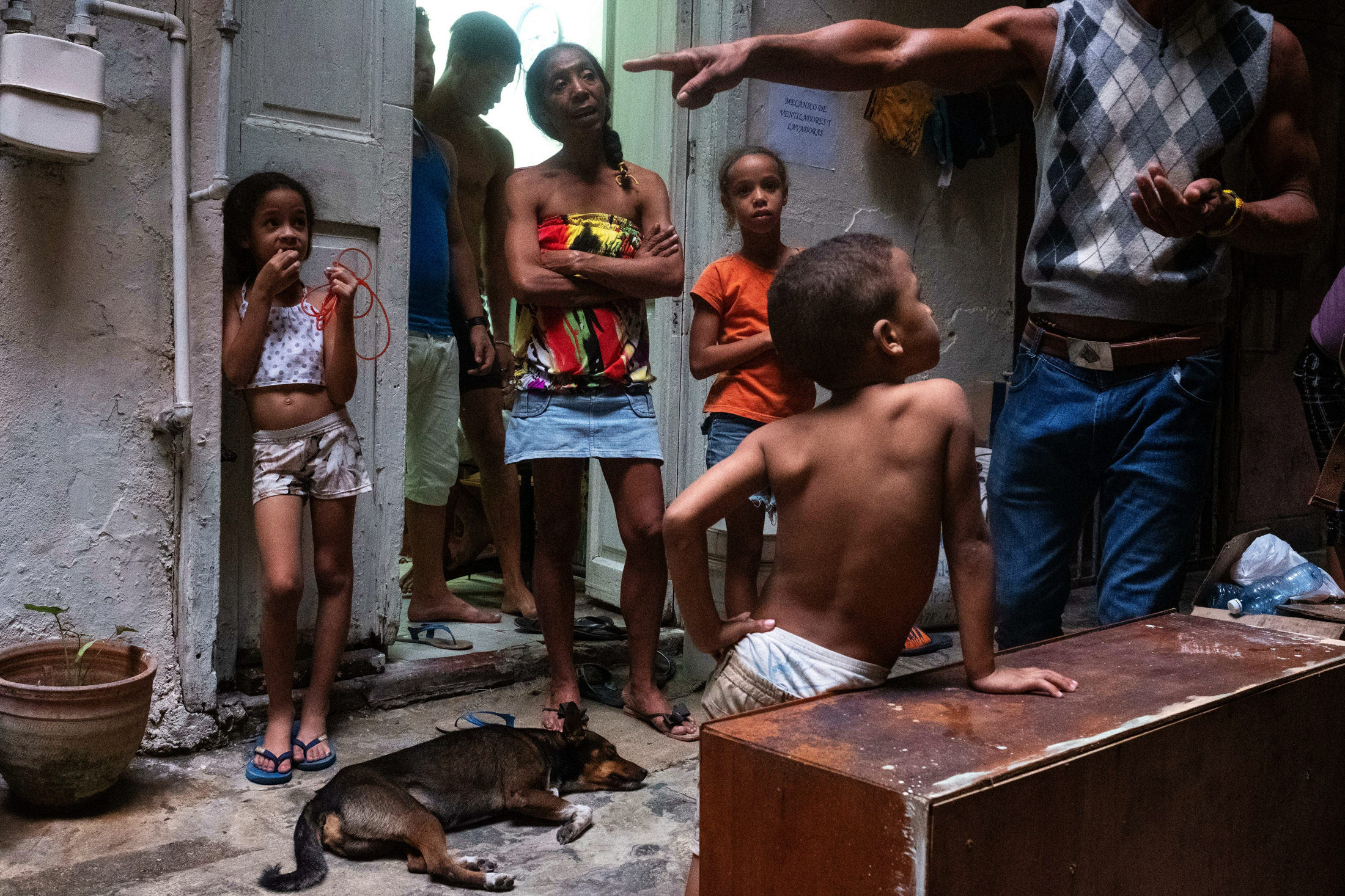 Cuban family in their house, man pointing and dog lying on ground